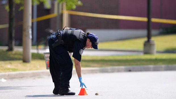A police officer places a marker on Danzig Street in Toronto on Tuesday, July 17, 2012, near the scene of a shooting. (The Canadian Press/Aaron Vincent Elkaim)