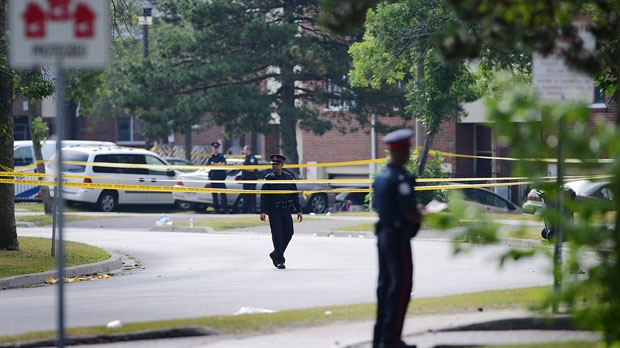 Police stand on guard on Tuesday July 17, 2012 on Danzig Street near the scene of a shooting where 19 people were injured and 2 confirmed dead at an outdoor barbecue that took place on Monday July 16, 2012 . (The Canadian Press/Aaron Vincent Elkaim)