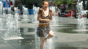 A woman cools down in the water sprinklers at Dundas Square during the extreme heat in Toronto on Tuesday, June 19, 2012.  (The Canadian Press/Nathan Denette)