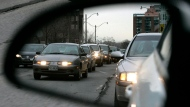 Commuters are reflected in a rearview mirror in rush hour traffic in Toronto. (The Canadian Press/J.P. Moczulski)