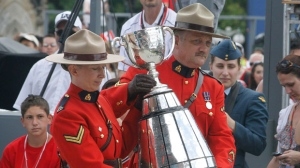 Two RCMP constables carry the Grey Cup, celebrating Canada Day on Parliament Hill Sunday, July 1, 2012 in Ottawa. (The Canadian Press/Fred Chartrand)