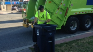 A Green For Life (GFL) Environmental employee collects garbage on Sheppard Avenue West in Toronto on Tuesday, Aug. 7, 2012. (CP24/Cam Woolley)
