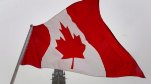 A Canadian Maple Leaf flag flies near the Peace tower on Parliament Hill in Ottawa on Feb. 15, 2012. (The Canadian Press/Adrian Wyld)