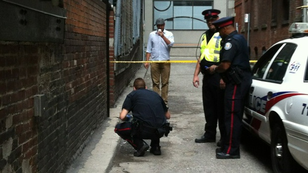 Toronto police officers investigate after a finger was found in a downtown alley Monday, Aug. 13, 2012. It turns out the finger was a fake that was used as a prop in a zombie film. (CTV/Tamara Cherry)