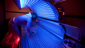 Lisa Shenton of Sunshine Tanning Studios cleans a tanning bed in North Vancouver, B.C., on Tuesday, March, 20, 2012. (The Canadian Press/Jonathan Hayward)