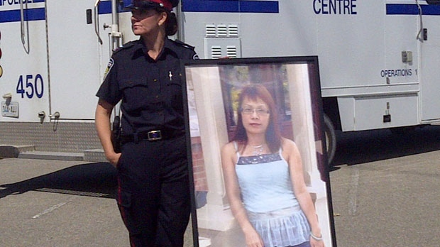 A police officer stands near a placard with a picture of Guang Hua Liu, who has been identified as the victim whose body parts were recently found in parks in Scarborough and Mississauga.