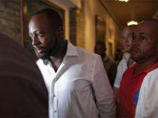 Haitian-born singer and presidential candidate Wyclef Jean, second left, walks surrounded by security after Haiti's Electoral Council rejected his candidacy in Port-au-Prince, Haiti, Friday, Aug. 20, 2010. (AP Photo/Ramon Espinosa)