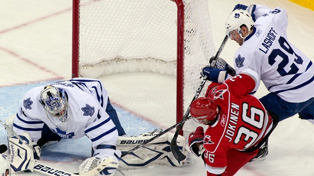 Carolina Hurricanes forward Jussi Jokinen gets taken to the ice by Toronto Maple Leafs defenceman Matt Lashoff with goalie James Reimer nearby during the first period of an NHL game in Raleigh, N.C., Wednesday, March 16, 2011. (AP Photo/Karl B DeBlaker)