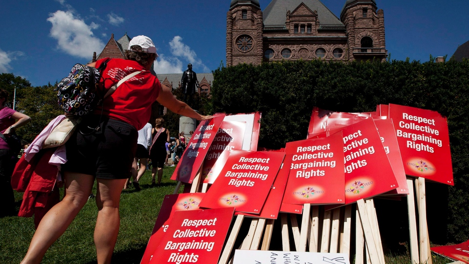A protester places a sign on a pile in front of Queen's Park following a rally against the