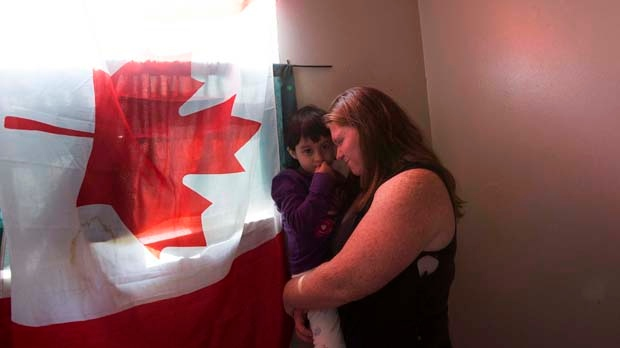 Kimberly Rivera, an American soldier who fled to Canada because she didn't want to serve in Iraq, holds her daughter Katie, 2, in their Toronto home on Thursday, Aug. 30, 2012. (Michelle Siu / THE CANADIAN PRESS)