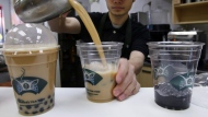 An employee of Ten Ren Tea in Flushing, Queens in New York, pours servings of popular bubble tea. (AP Photo/Kathy Willens)