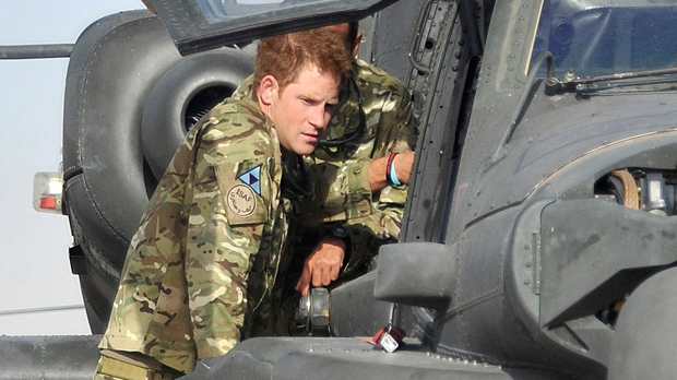 Prince Harry is shown an Apache helicopter by a member of his squadron, obscured behind, at Camp Bastion in Afghanistan on Friday, Sept. 7, 2012. (Cpl. Paul Morrison / Army Photographer, MOD)