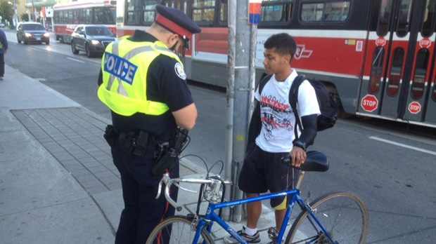 A Toronto police officer speaks to a cyclist during a bicycle safety campaign at Danforth and Broadview avenues Monday, Sept. 10, 2012. (CP24/Cam Woolley)