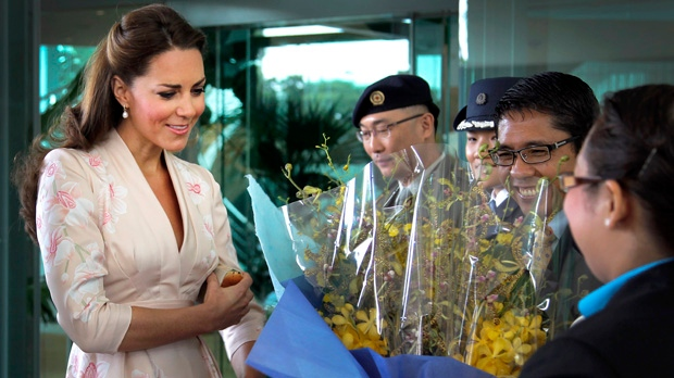 Kate, the Duchess of Cambridge, reacts as she receives flowers upon arrival at the VIP terminal of Changi International Airport in Singapore on Tuesday, Sept. 11, 2012. (AP Photo/Wong Maye-E, Pool)
