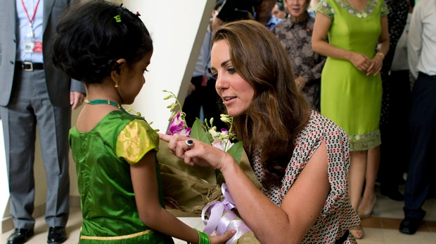 Kate, the Duchess of Cambridge, receives flowers from a girl during her visit to Strathmore Green, a precinct in Queenstown, a residential district of Singapore, on Wednesday, Sept. 12, 2012. (AP Photo/Nicolas Asfouri, Pool)