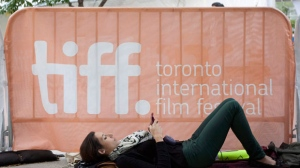 "A woman waits behind a barricade prior to the gala for the film ""Starbuck"" during the Toronto International Film Festival in Toronto on Wednesday, Sept. 14, 2011. (The Canadian Press/Darren Calabrese)"