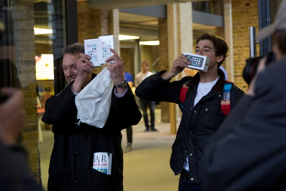 Norman Hicks, left, and Jess Green, aged 15, the first two customers at the front of the queue, pose for photographers with boxed iPhone 5s handsets as they leave the Apple Store in Covent Garden, London, Friday, Sept. 20, 2013. (AP / Matt Dunham)