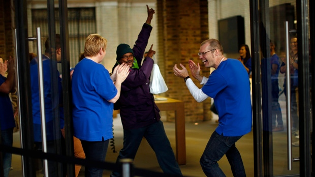 Apple workers applaud a customer posing after he purchased an iPhone 5 at the company's store in London on Friday, Sept. 21, 2012. (AP Photo/Matt Dunham)
