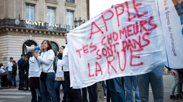 "Former and current Apple employees - some of them holding a banner reading ""Apple, your unemployed workers are in the street"" - protest outside an Apple store in Paris on Friday, Sept. 21, 2012. (AP Photo/Thibault Camus)"