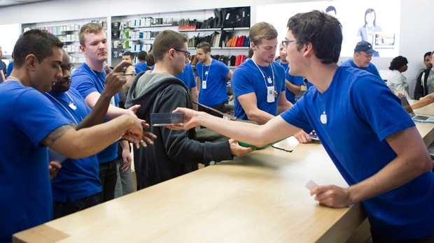 Apple staff hand over Apple iPhone 5s as customers queue for the new model at the Apple store in Toronto's Eaton Centre on Friday, Sept. 21, 2012. (The Canadian Press/Chris Young)