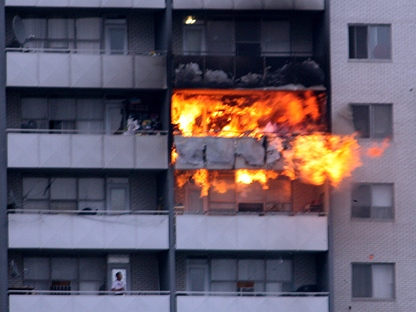 A resident looks up as flames shoot from a 24th floor apartment Friday afternoon. (CP24 MyBreakingNews - Jeff Riffle)