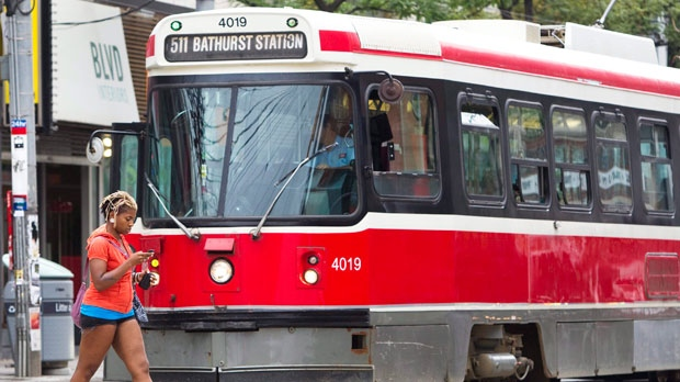 A pedestrian uses a mobile phone while walking in front of a streetcar in downtown Toronto Wednesday, Aug. 3, 2011. (The Canadian Press/Darren Calabrese)