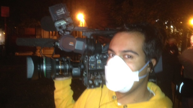 CP24 cameraman Tom Stefanac wears a mask provided by Toronto Fire Services at the scene of a blaze on George Street on Thursday, Oct. 4, 2012. (CP24/Cam Woolley)