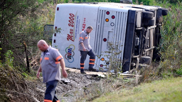 Workers check out a bus which overturned coming off at an exit ramp on Route 80 in Wayne, N.J. Saturday, Oct. 6, 2012. The chartered tour bus from Toronto carrying about 60 people overturned on an interstate exit ramp. (AP Photo/Bill Kostroun)