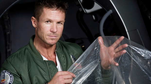 In this Feb. 23, 2012, photo provided by Red Bull Stratos, pilot Felix Baumgartner shows a piece of balloon material during the Red Bull Stratos egress training in Lancaster, Calif. (AP Photo/Red Bull Stratos, Joerg Mitter)