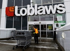A Loblaws employee brings in shopping carts in Toronto on Wednesday, Feb. 18, 2009. (THE CANADIAN PRESS/Nathan Denette)