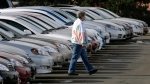 An unidentified buyer searches through long lines of unsold 2007 Corolla and Camry sedans at a Toyota dealership in Boulder, Colo., Feb. 18, 2007. (AP / David Zalubowski)