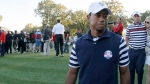 USA team member Tiger Woods walks off the course as Europe celebrates their win at the Ryder Cup golf tournament Sunday, Sept. 30, 2012, at the Medinah Country Club in Medinah, Ill. (AP Photo/Charles Rex Arbogast)