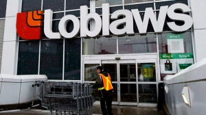 A Loblaws employee brings in shopping carts in Toronto on Wednesday, Feb. 18, 2009. (Nathan Denette / THE CANADIAN PRESS)